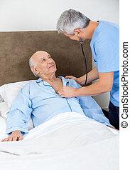 Caretaker Checking Senior Man With Stethoscope