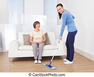 Caretaker Cleaning Floor While Woman Sitting On Sofa
