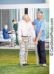 Caretaker Comforting Senior Man While Assisting Him At Lawn