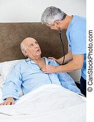 Caretaker Examining Senior Man With Stethoscope