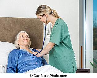 Caretaker Examining Senior Woman At Nursing Home