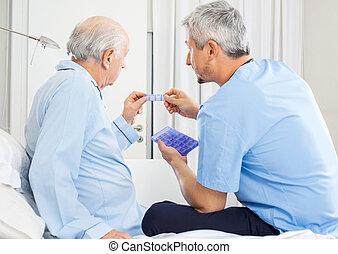 Caretaker Guiding Prescription To Senior Man