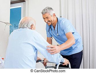 Caretaker Helping Senior Man To Use Walking Frame
