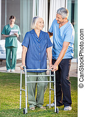 Male caretaker helping senior woman to use walking frame with female nurse in background at nursing home lawn