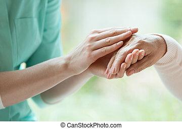 Caretaker massaging pensioner's hand - Young caretaker...