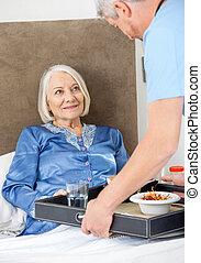 Caretaker Serving Breakfast To Happy Senior Woman