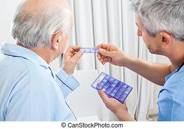 Male caretaker showing prescription medicine to senior man in bedroom at nursing home