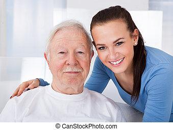 Portrait of young female caretaker with senior man at nursing home