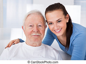 Caretaker With Senior Man At Nursing Home - Portrait of...
