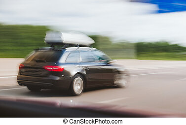 Cargo carrier on top of wagon car driving fast on highway...