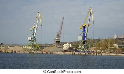 cargo crane in the river port view from the sea to ship loading