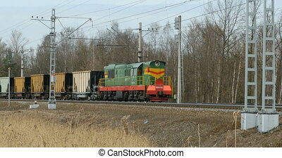 Cargo diesel locomotive with railcar in motion
