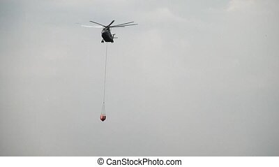 Cargo fire helicopter with suspended spillway ladle is...