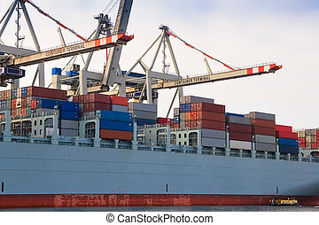 Unloading huge cargo freight container ship at harbour terminal