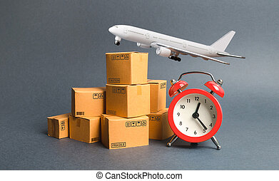Cargo plane, stack of cardboard boxes and a red alarm clock. Express air delivery concept. Temporary storage, limited offer and discount. Optimization of logistics, improving efficiency