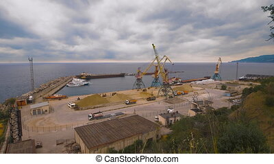 Cargo port. Crane with bucket makes loading sand into a truck.