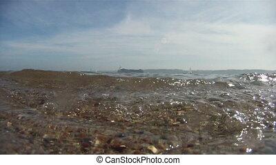 Cargo ship and boats on horizon