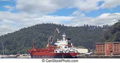 cargo ship at a port near the mountains