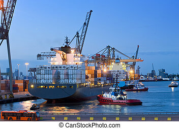 Cargo ship docking - Several tugs and support vessels,...