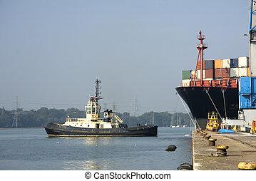 Cargo ship emerges from dock, Southampton, UK