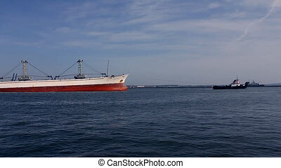 Cargo ship leaves port with tug assistance