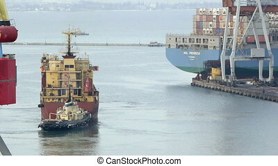 Cargo ship leaves port with tugs assistance