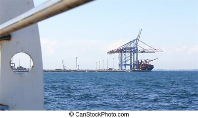 Cargo Ship Loading In Sea Port - Crane loads containers on a...