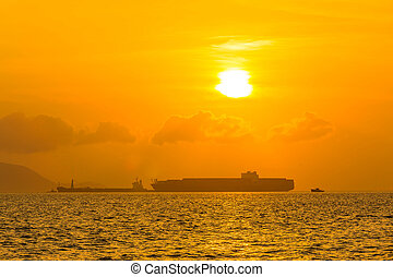 Cargo ship on sea at sunset