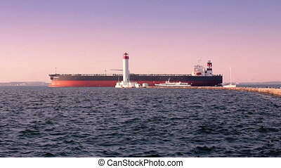 Cargo ship passing by lighthouse at the sea port