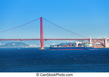 Cargo ship passing under Golden Gate Bridge, USA