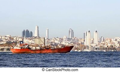 Red cargo ship moves on front of the city