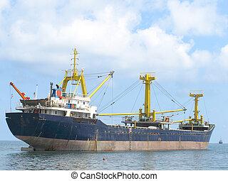Cargo ship rides at anchor near a seacoast