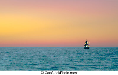Cargo ship sailing during colorful sunset, Crete, Greece.
