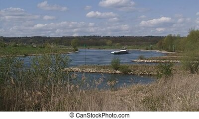 Cargo ship sailing in bend of river IJssel, The Netherlands.