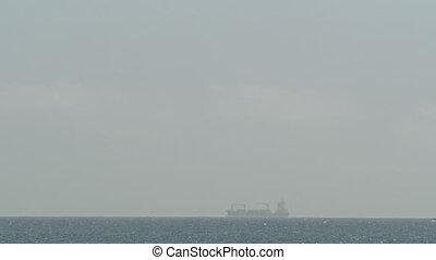 Cargo ship sailing in quiet sparkling ocean - Ocean skyline ...