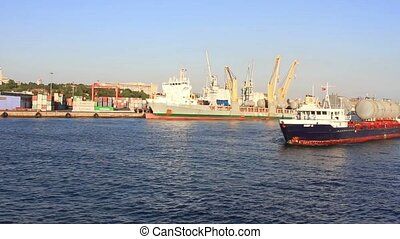 Cargo ship sails from harbor with loaded large gas pipes.