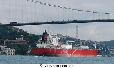 Cargo ship sails under the bridge Ataturk.
