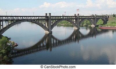 Cargo ship sails under the bridge.