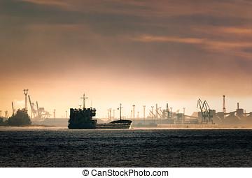 Cargo ship silhouette entering a port of Riga at the morning