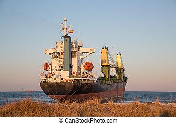 Cargo Ship - Rear view of cargo ship aground near beach