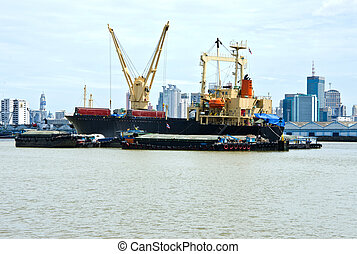 cargo ship with crane on the river