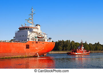 Cargo ship with tug boat - Cargo ship out of the port of ...
