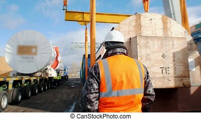 Cargo shipping - a man worker standing on the construction site and controls the process