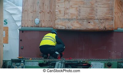 Cargo shipping - men working on the construction site - unhook the cargo from the truck