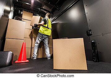 Cargo Van Loading by Worker. Man Carrying Boxes In the Cargo...