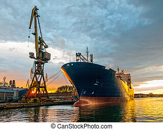 Cargo vessel - Cargo ship in the harbor at sunset. Gdansk,...