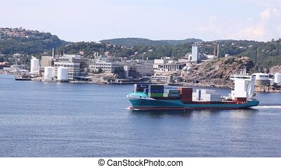 Cargoship loaded with containers draw away against landscape