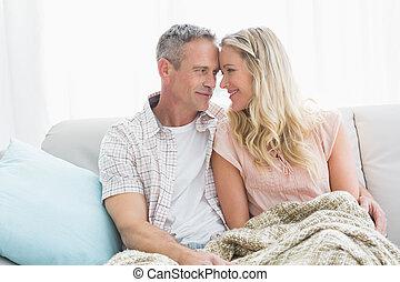 cariñoso, pareja, se sentar sobre sofá, debajo, manta