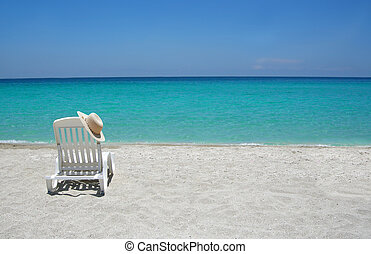 Caribbean beach chairs - Empty tropical beach chair with hat...