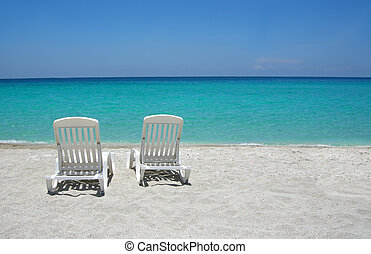 Caribbean beach chairs - Empty tropical beach chairs on sand...
